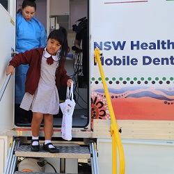 Dentist checking teeth of a school boy in a mobile dental clinic