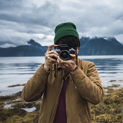 Man in beanie taking a photo next to a lake on an overcast day