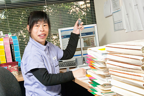 Yuan, an Asian woman with a disability, working at a desk with files